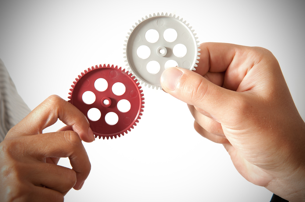 partnership concept with two hands holding two cogs