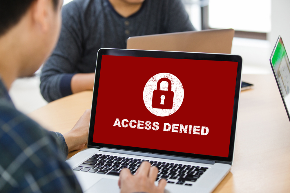 laptop screen shows red warning with words access denied