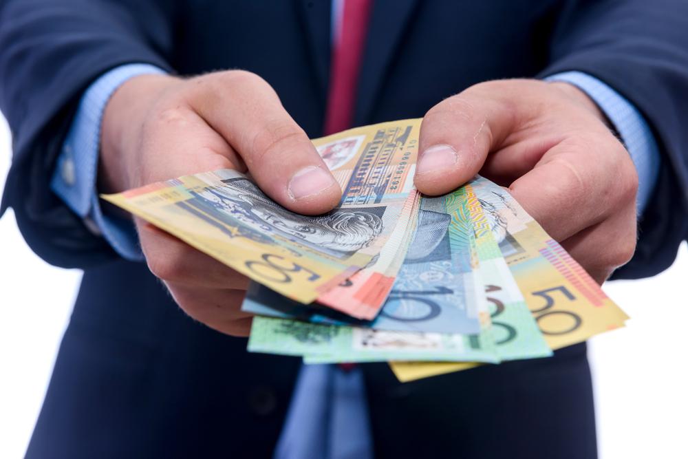 Businessman offering Australian bank notes
