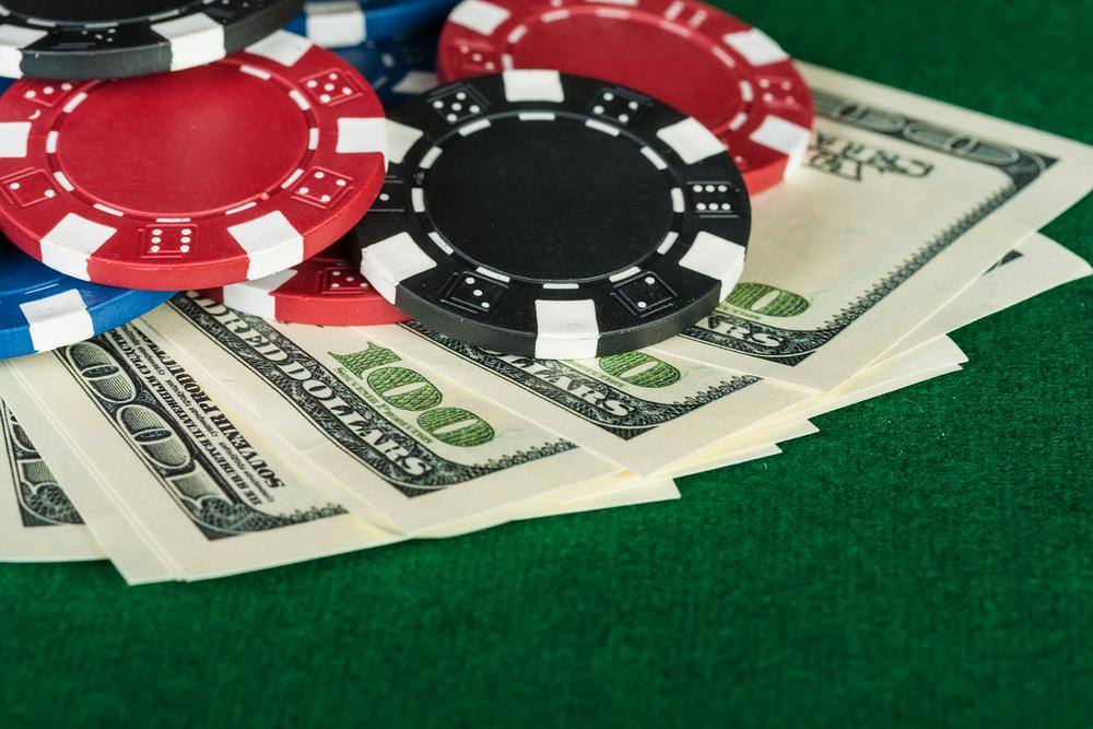 poker chips and hundred-dollar bills on green poker table