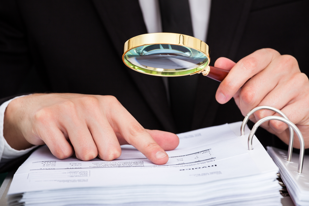 Businessperson holds magnifying glass while examining an invoices file