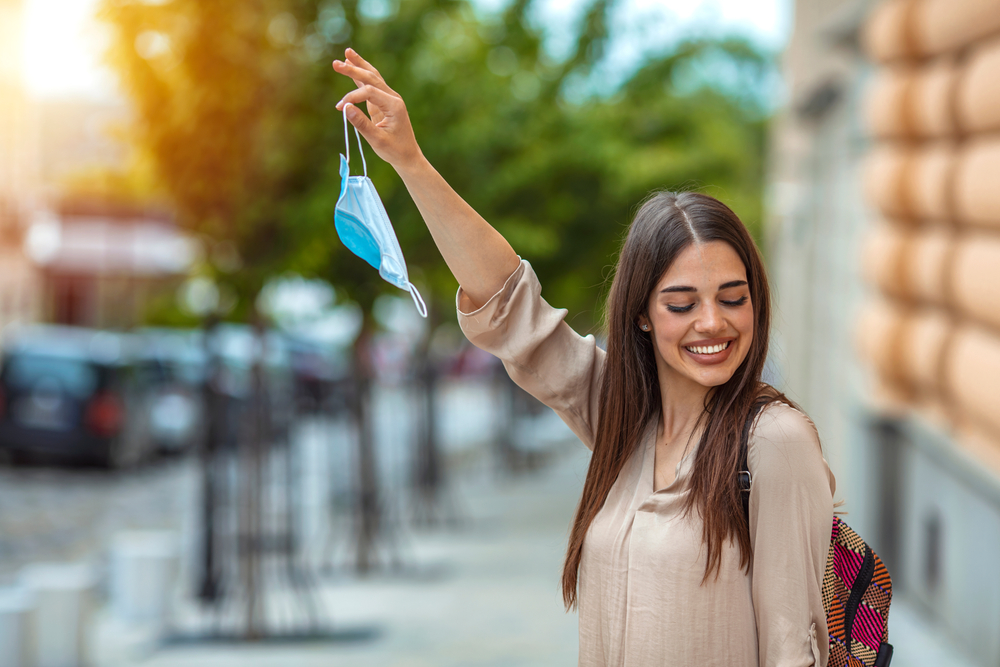 woman happily removes surgical face mask in street