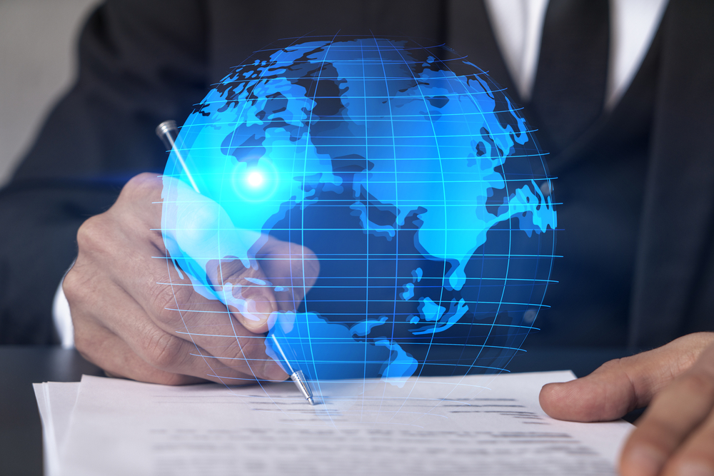 holographic image of the globe in front of businessman signing contract