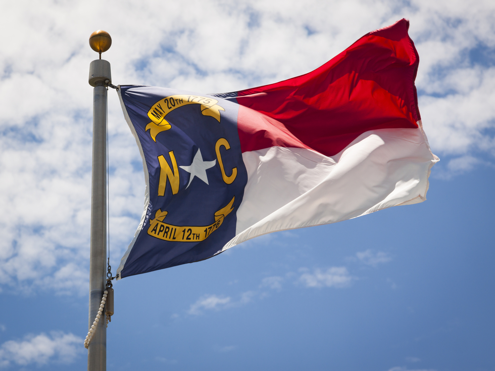 flag of North Carolina against a blue sky and clouds backdrop