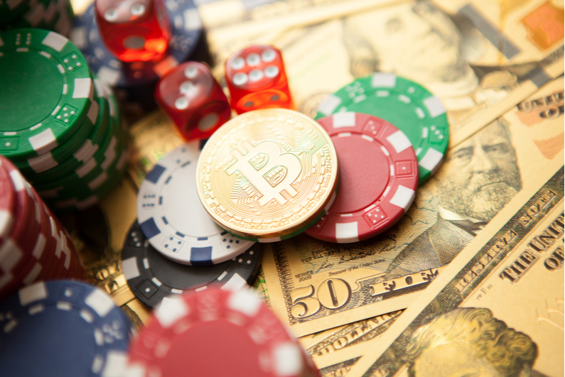 Physical mock Bitcoin and poker chips on top of cash