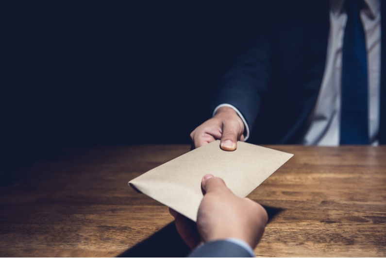 Businessman handing envelope to across a table