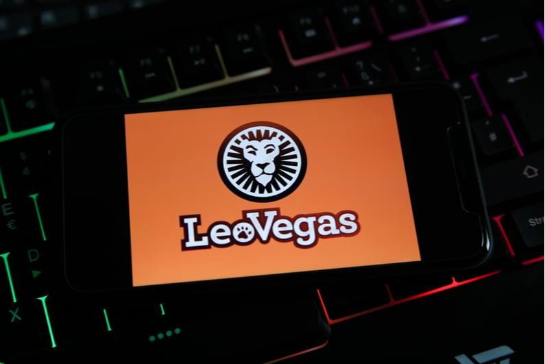 LeoVegas splash screen on a smartphone resting on a laptop keyboard