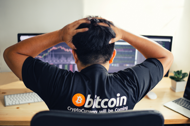 Man in Bitcoin shirt upset at charts on computer