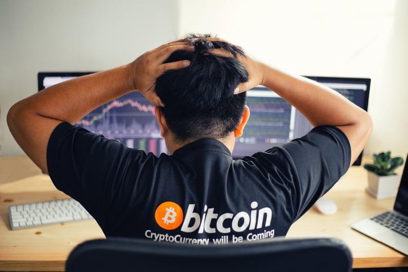 Man in Bitcoin shirt upset at charts on computer