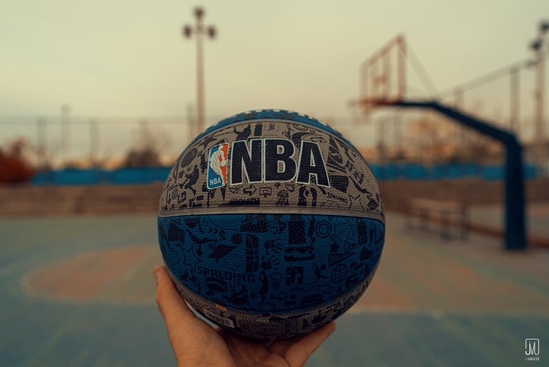 Hand holding NBA logoed blue and grey basketball at an outdoor court