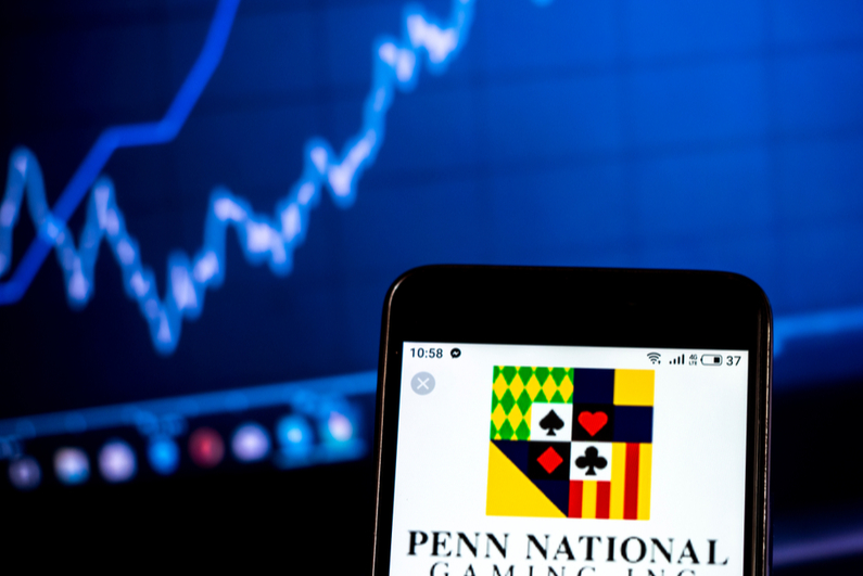 Penn National gaming logo on a smartphone with a stock chart in the background