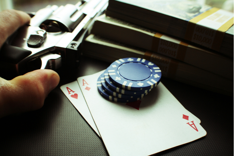 Person holding gun on table with cards, chips, and cash