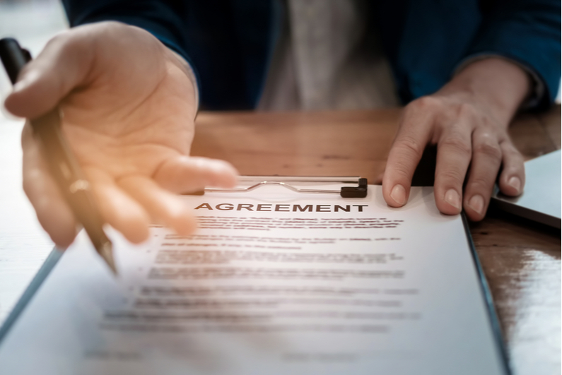 Business person sliding agreement across table to be signed