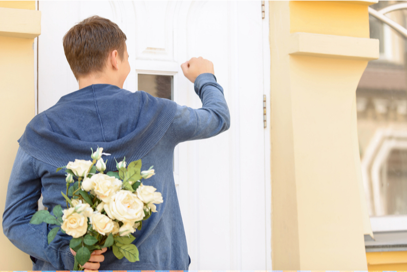 Young man with bouquet of flowers knocking on door