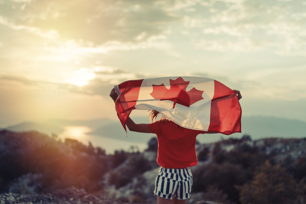 Female holds Canada flag while looking at the setting sun