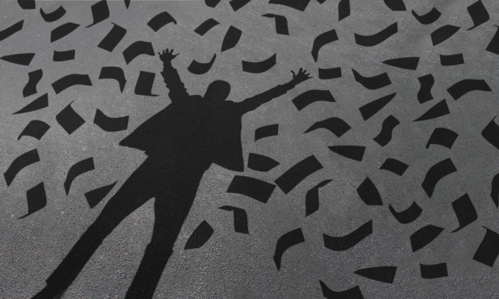 silhouette of man with arms up in victory as paper money rains down on him
