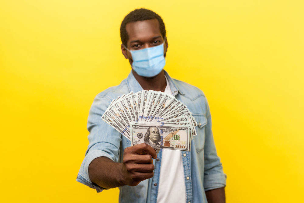 Man in surgical mask holds up American hundred-dollar bills