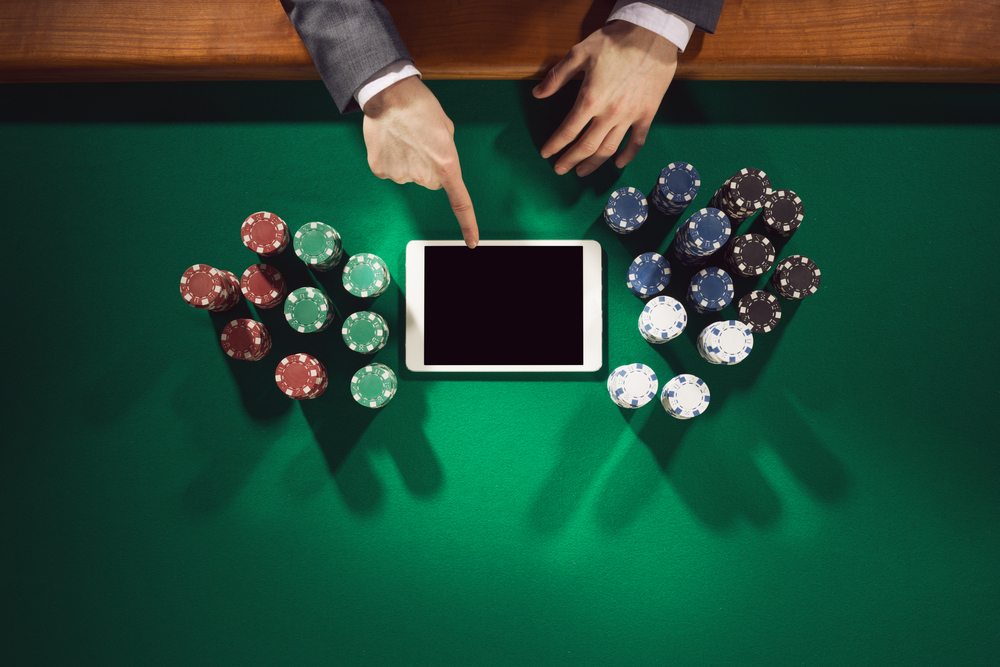 Male hands touching tablet screen on green felt poker table surrounded with poker chips