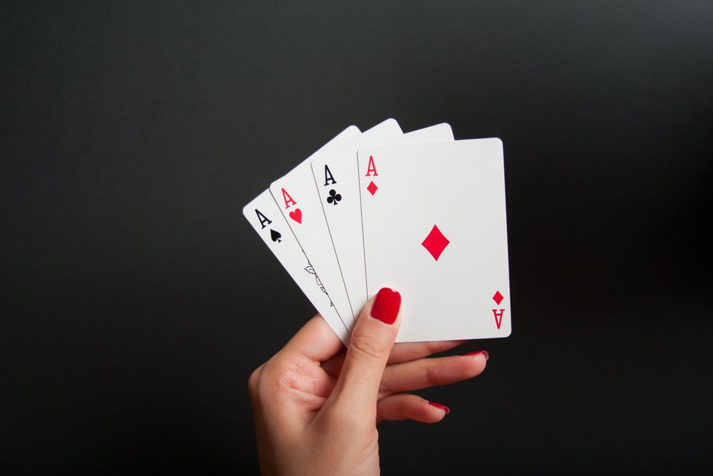 woman's hands hold four of a kind poker cards