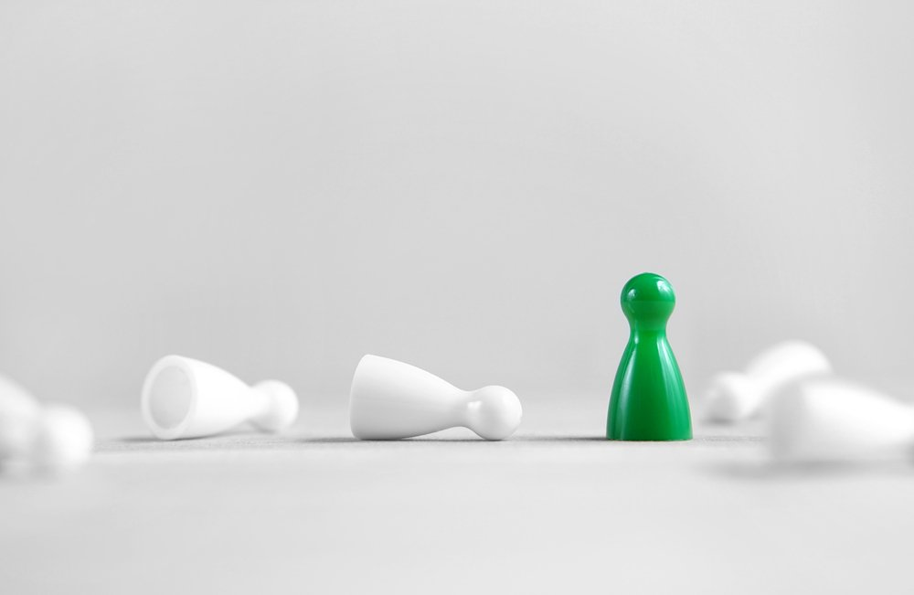 one green pawn standing amid white knocked-over pawns