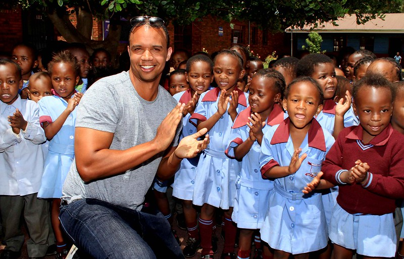 Poker Player Phil Ivey poses with children singing