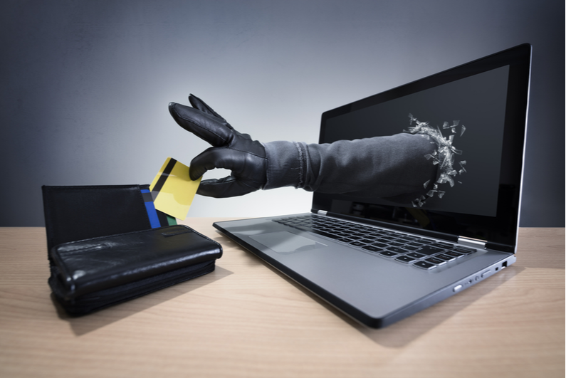 Gloved hand coming out of a laptop monitor and stealing a credit card from a purse