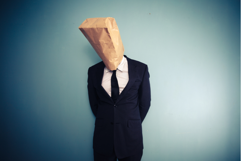 Man in a suit with a bag over his head