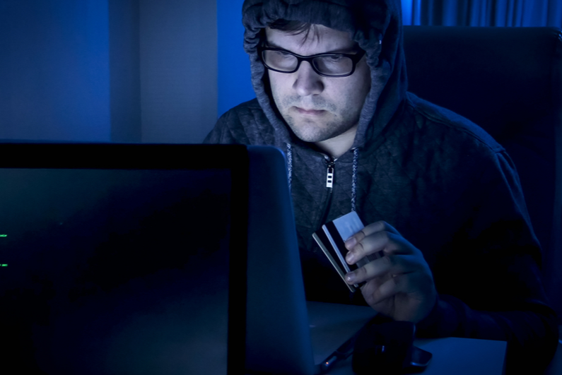 Shady looking guy holding credit cards at computer