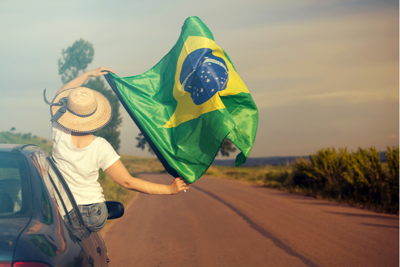 Woman leaning out of a car window flying a Brazil flag