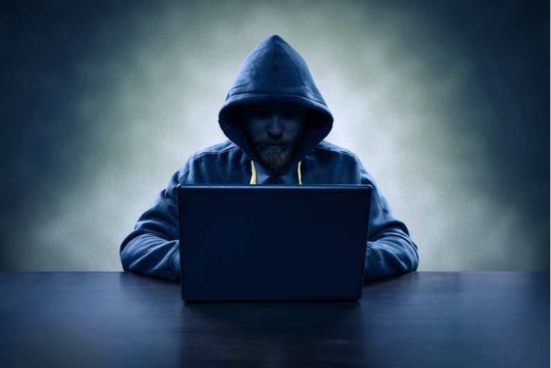 Shadowy man in a hoodie sitting at a laptop