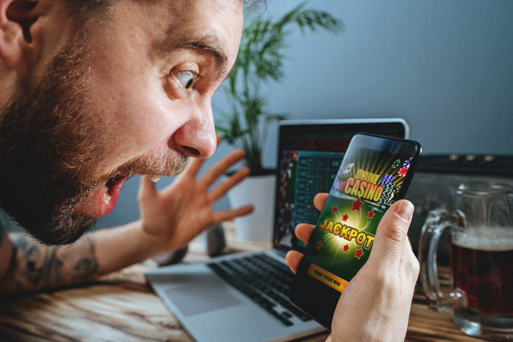 man puts on an excited face as he wins a mobile casino game
