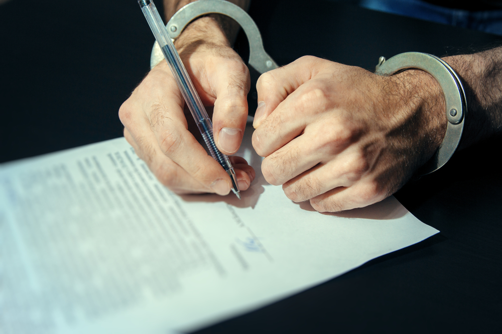 handcuffed person signing a guilty plea agreement