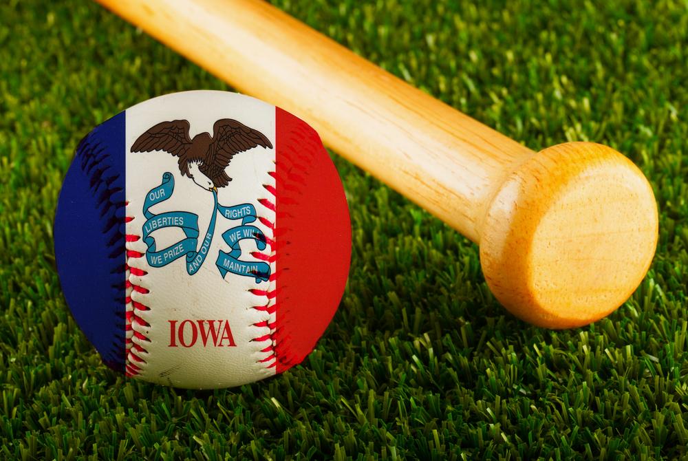 baseball with Iowa flag lies on grass pitch near bat