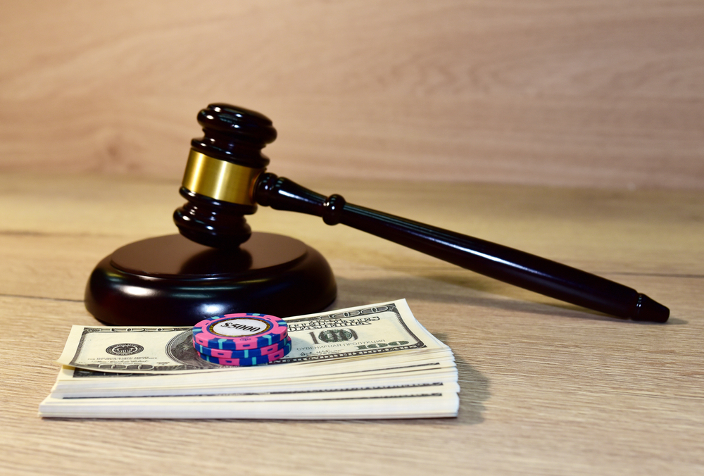 Wooden gavel with dollars and poker chips