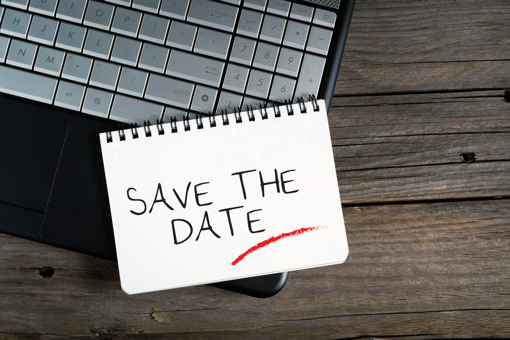 Save the date note written on a paper notepad