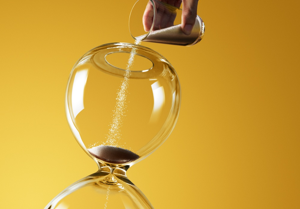 hand pours sand into hourglass