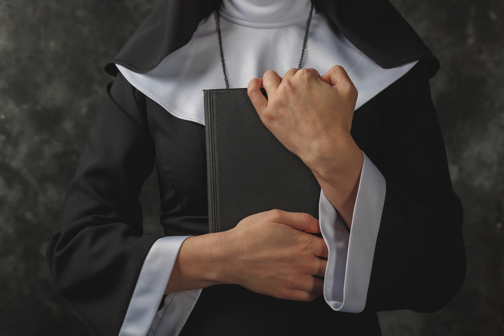 nun holds book in hands