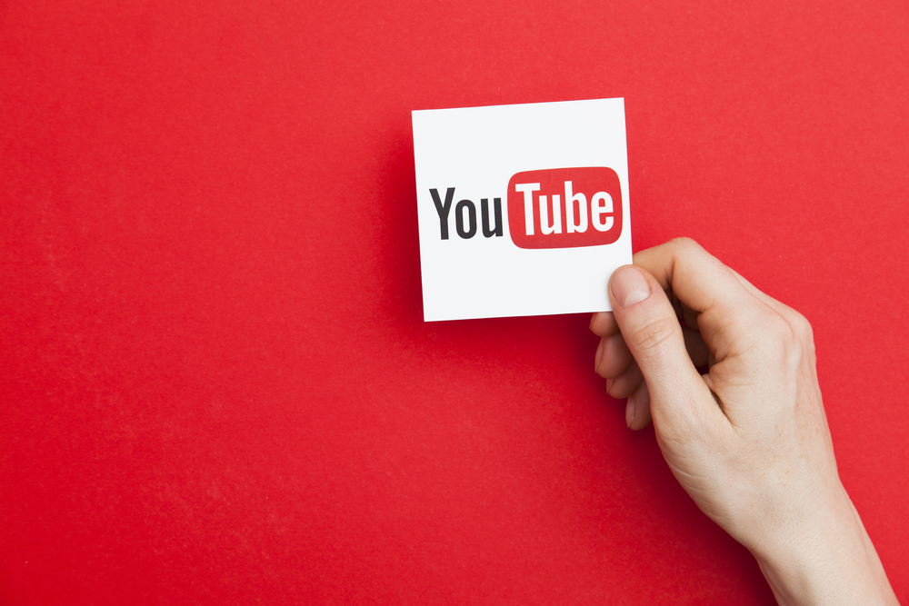hand holding YouTube logo against red background