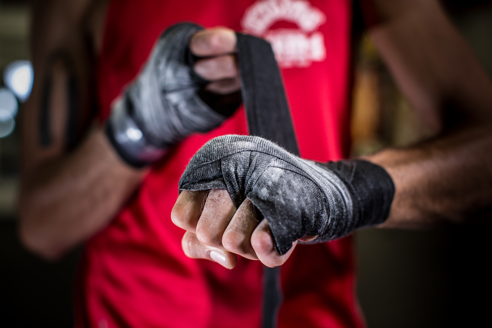 boxer wrapping up his hands with black fabric