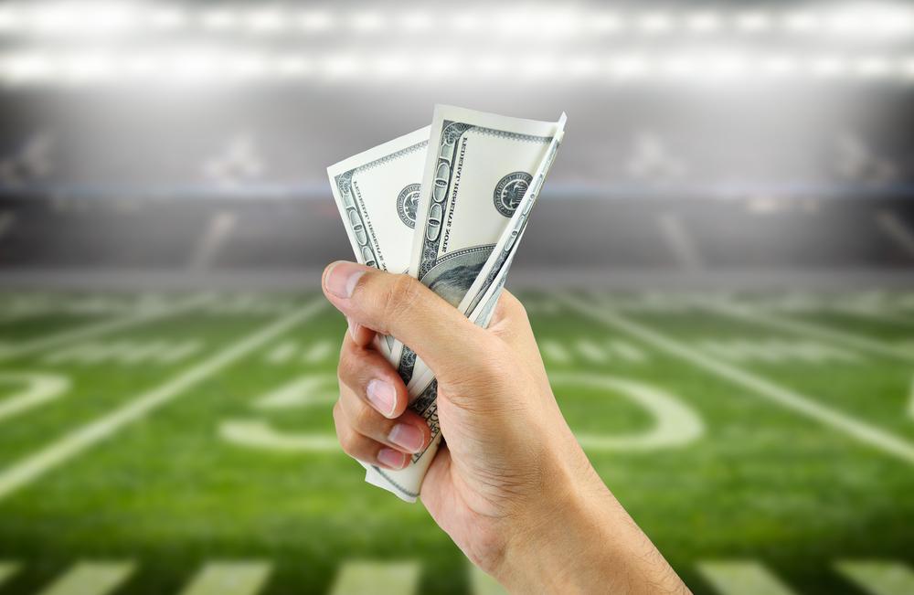 A hand gripping money