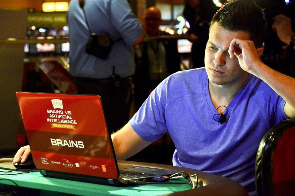 Doug Polk at his laptop on a poker table