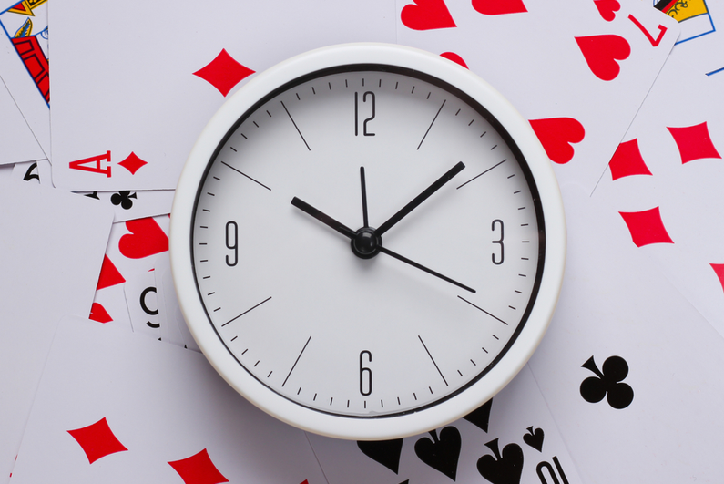 Clock on top of playing cards