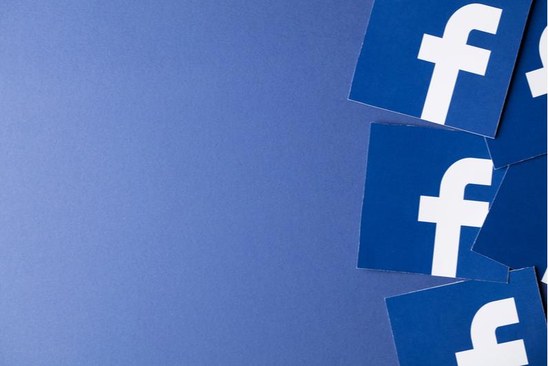 Facebook logo printed on blue paper squares