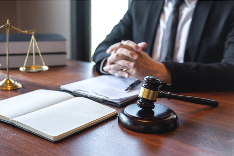 Lawyer at a desk with paperwork and a gavel