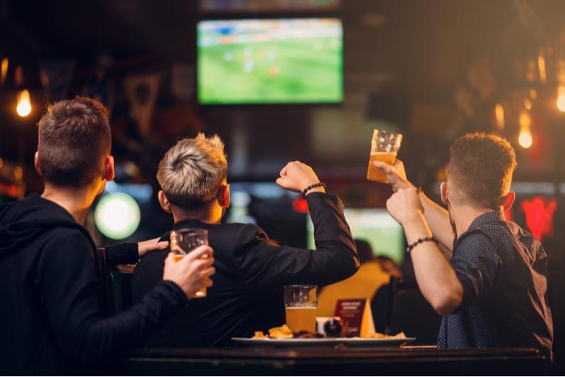 Three men cheering at a sports bar