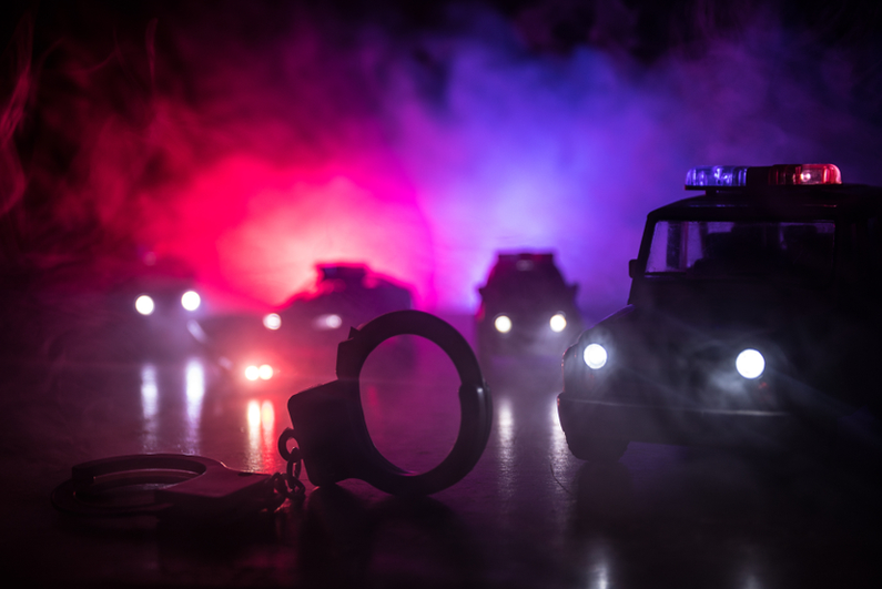 Police cars at night with handcuffs in the foreground