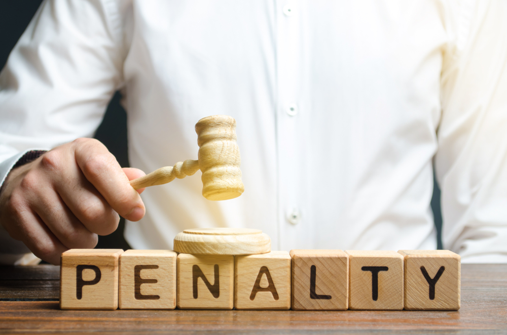 letter cubes spell out penalty as hand holds a judge's gavel