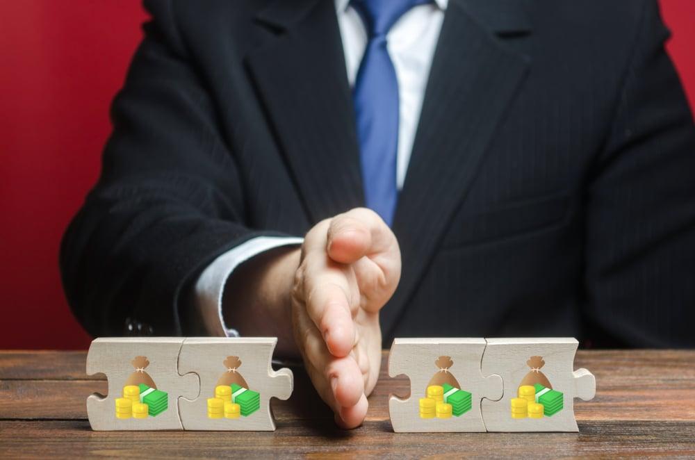 A businessman splitting bricks with money symbols