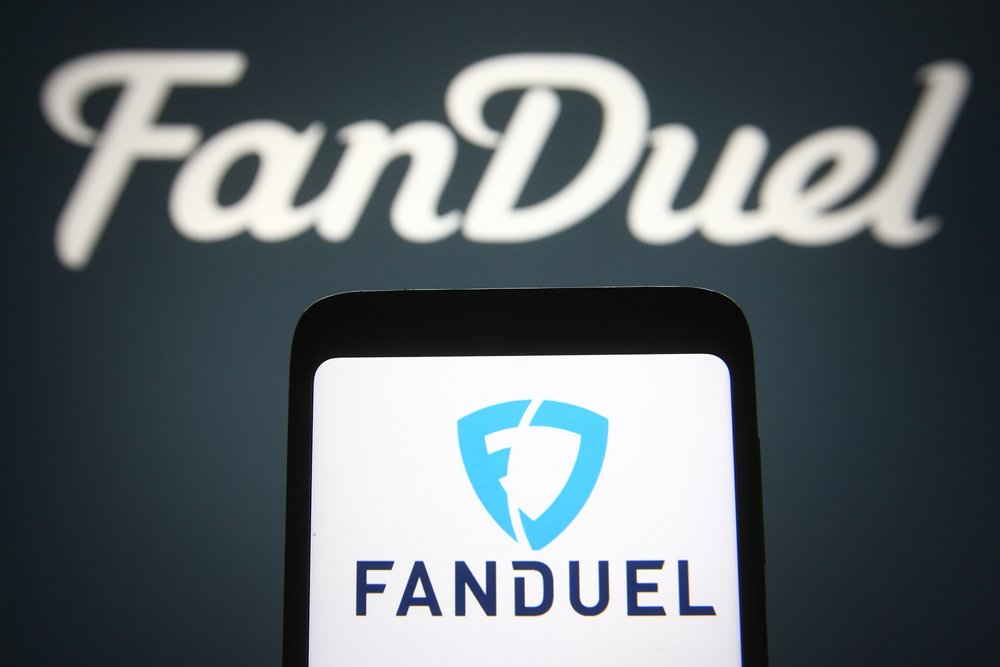 FanDuel logo on smartphone and on black background