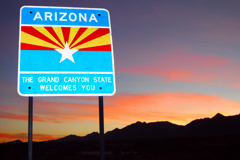 Arizona welcome road sign against a dusky pink sky